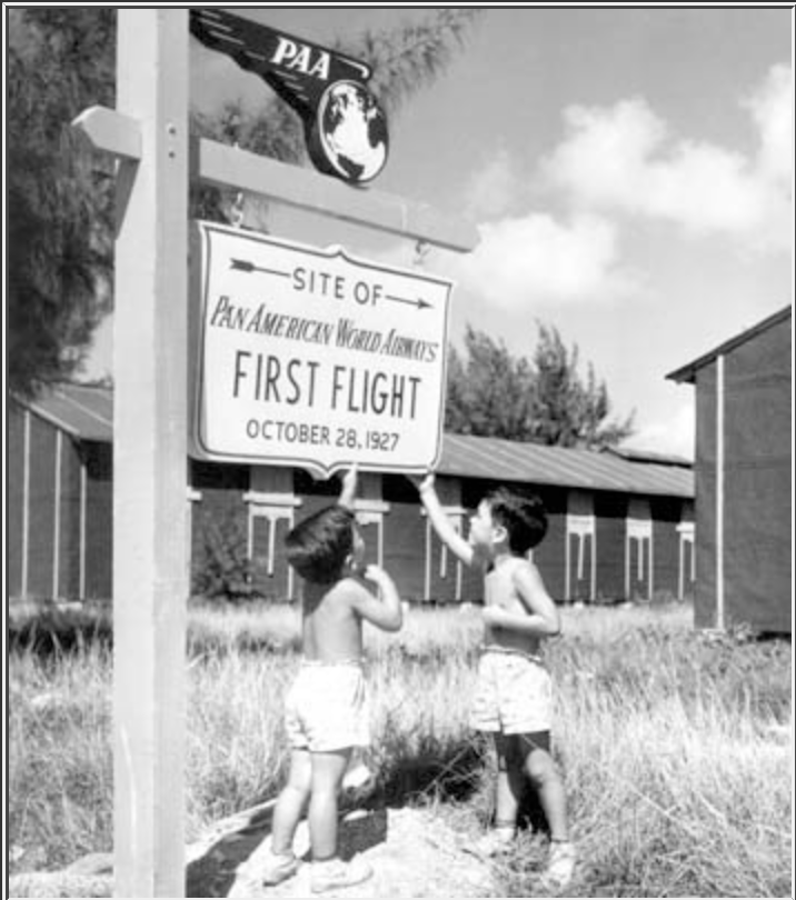 Children stand beneath a PAA sign marking the PAA's first international flight.