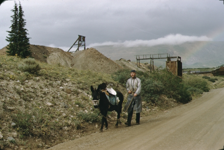 A man with a burro walks from a mine entrance