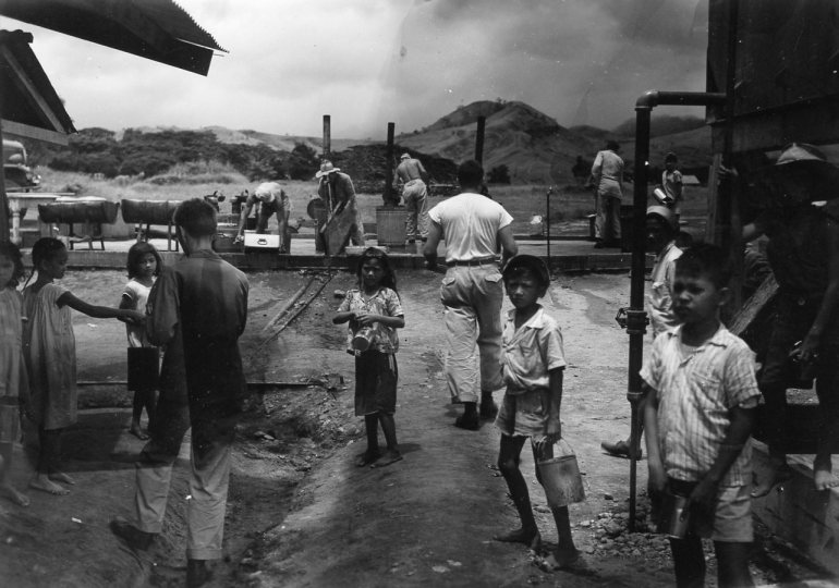 Filipino children play amongst American service personnel after liberation
