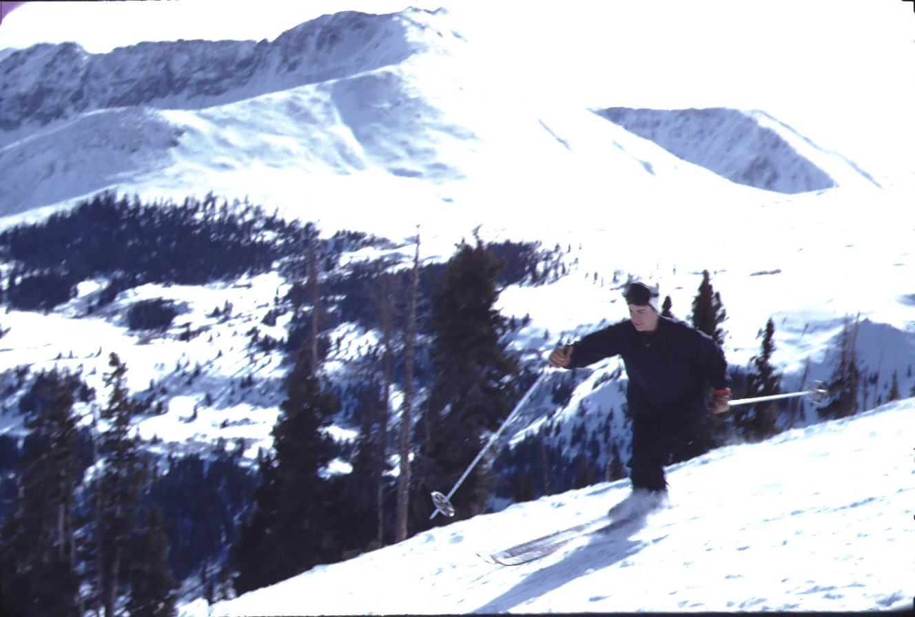 Vintage color photo of a woman skiing downhill at Climax ski area in front of Mount Arkansas