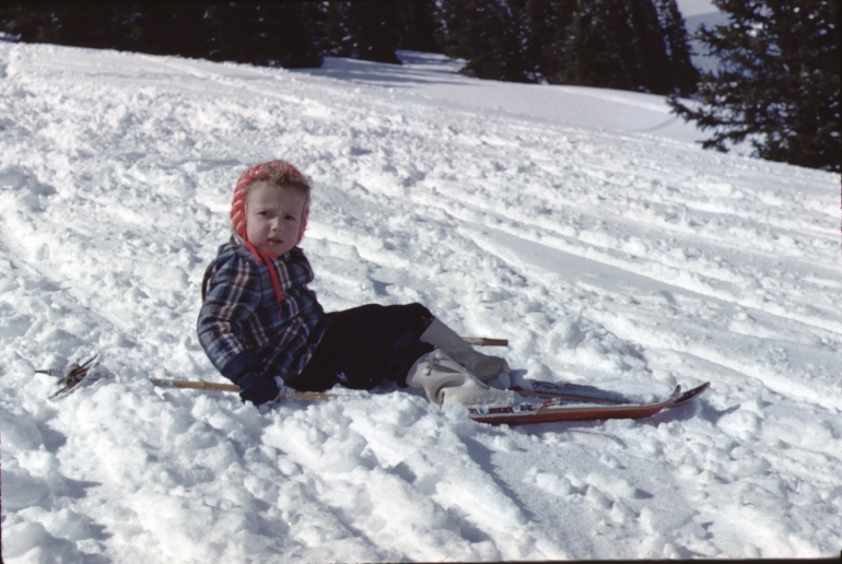 Vintage photo of a little girl who has fallen off her skis.