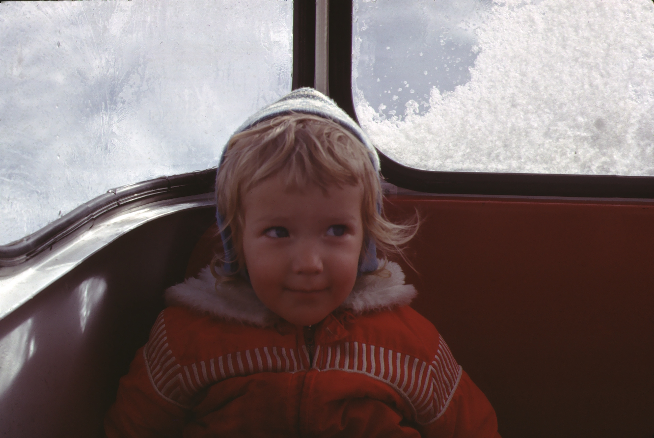 Vintage photo of a little girl riding in a ski gondola