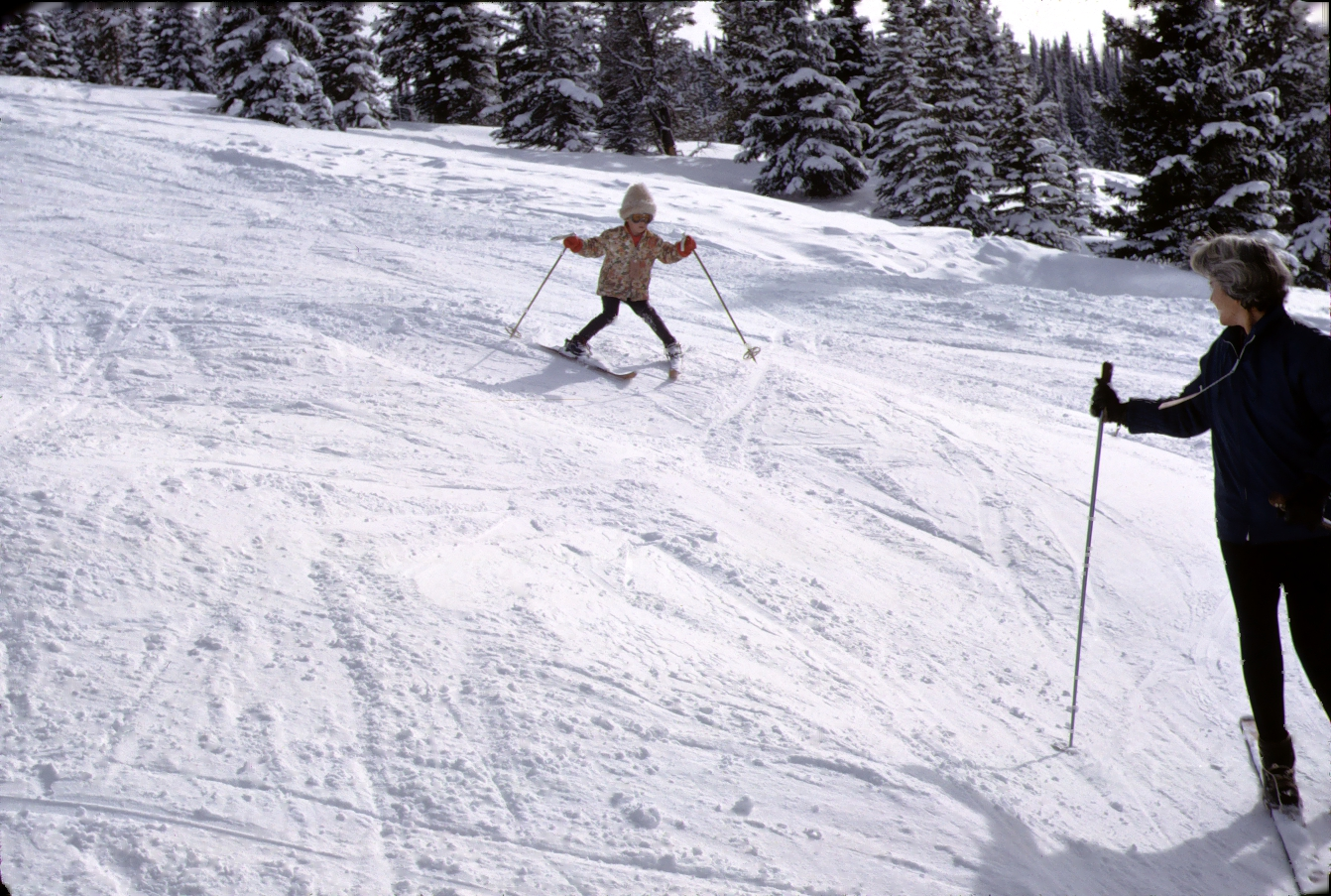 Vintage photo of a little girl skiing down a mountain while her mother looks on.