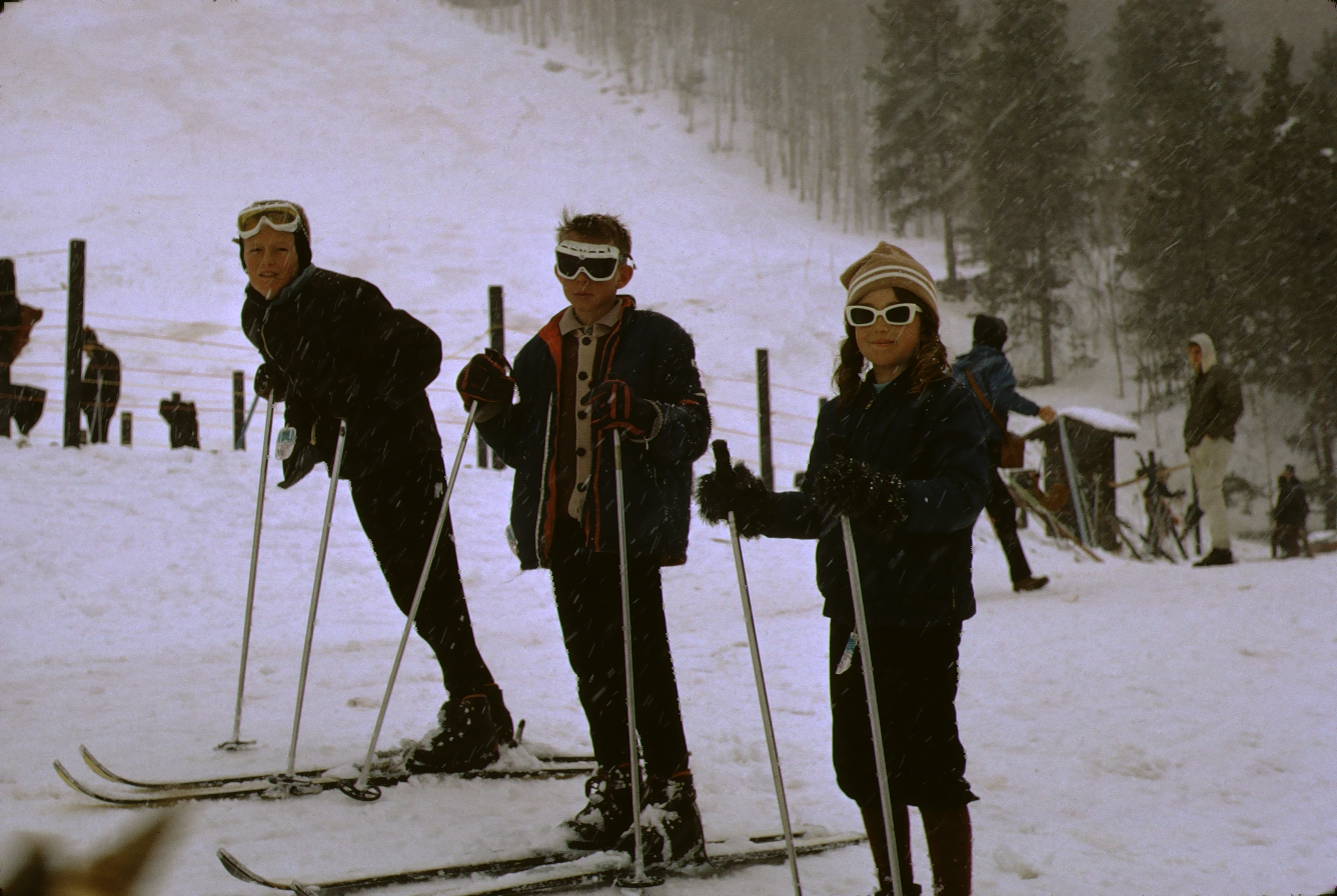 Color photo of Debbie Rutzebeck and unknown males at ski area taken by W. R. Allen